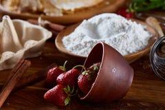 在一个被翻转的碗的红色新鲜的草莓在烘烤背景,特写镜头,选择聚焦 免版税库存图片