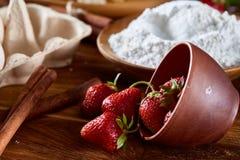 在一个被翻转的碗的红色新鲜的草莓在烘烤背景,特写镜头,选择聚焦 免版税图库摄影