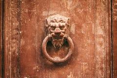 在一个被风化的房子前门的老生锈的敲门人狮子头 免版税库存照片