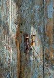 在一个被风化的老木蓝色门的老生锈的匙孔 免版税库存图片