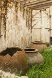 在一个被破坏的房子的地板上的残破的罐 免版税库存照片