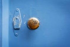 在一个被绘的蓝色门的老黄铜门把手 免版税图库摄影