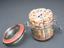 在一个装于罐中的瓶子的欧洲金钱 库存图片