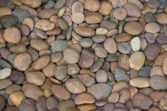 在一个装饰庭院的各种各样的颜色腐蚀从河和堆的被环绕的石头 免版税库存图片