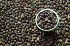 在一个装饰杯子的咖啡粒 顶视图 烤咖啡豆  免版税库存图片