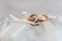 在一个装饰枕头的婚戒有珍珠和丝带的 库存照片