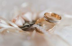 在一个装饰枕头的婚戒有珍珠和丝带的 免版税库存图片