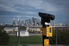 在一个观察台的谈的望远镜在格林威治皇家公园有在女王/王后的房子和伦敦市的一个看法 免版税库存照片
