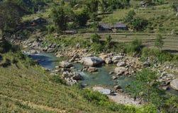 在一个谷的山小河接近村庄,北越南 免版税库存照片