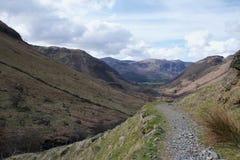 在一个谷附近的边的石小径在英国湖Distrit坎布里亚郡 免版税库存图片