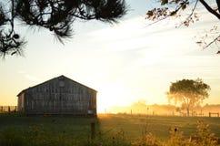 在一个谷仓后的日出在一个有雾的早晨 免版税图库摄影