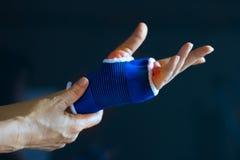 在一个资深手腕子的剧痛, safty在从舒展的绷带,上色在深蓝背景的红色 免版税库存照片