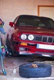 在一个车库的红色老汽车没有轮子 免版税库存照片