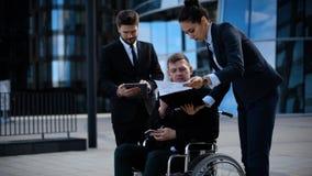 在一个轮椅的商人有在办公楼之外的同事的谈论紧靠成交和事务 股票录像
