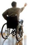 在一个轮椅的残疾开会在窗口附近的屋子里 库存照片
