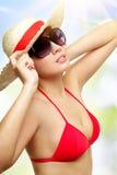 在一个轻的背景的女孩佩带的太阳镜 免版税库存图片