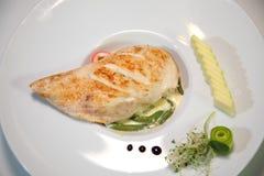 在一个辣调味汁的被烘烤的鸡内圆角与菜 图库摄影