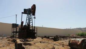在一个运作的油田上油pumpjacks在巴库,阿塞拜疆 运转的油泵剪影和老生锈的铁滚磨 股票视频
