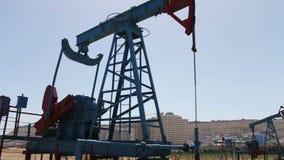 在一个运作的油田上油pumpjacks在巴库,阿塞拜疆 运转的油泵剪影在蓝天背景的和 影视素材