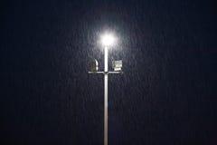 在一个运动场的光晚上在雨中 免版税库存图片
