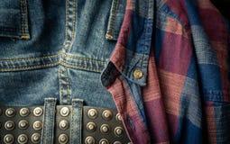 在一个退色的对的皮带红色和蓝色方格的衬衣蓝色牛仔裤和细节  免版税图库摄影