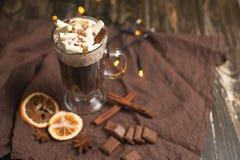 在一个透明杯子的巧克力热饮有被鞭打的奶油的和肉桂条、香料、坚果和可可粉在一土气木backgr 库存图片