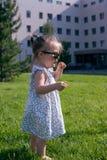 在一个逗人喜爱的矮小的小孩女孩的看法太阳镜的在城市公园在一个晴朗的夏日 库存照片