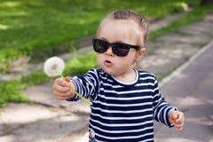 在一个逗人喜爱的矮小的小孩女孩的看法太阳镜的在城市公园在一个晴朗的夏日 免版税库存照片