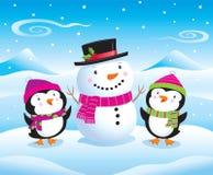 在一个逗人喜爱的雪人旁边的小企鹅 库存图片