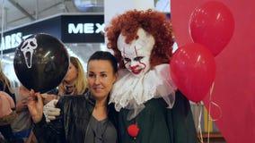 在一个邪恶的小丑旁边的女孩立场有红色球的在万圣夜庆祝的一张照片的 股票录像