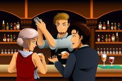 在一个酒吧的夫妇与侍酒者 免版税图库摄影