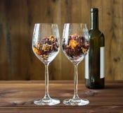 在一个酒杯和酒瓶的秋叶在木桌背景 免版税库存照片
