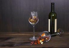 在一个酒杯和酒瓶的秋叶在木桌背景 免版税库存图片