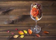 在一个酒杯的秋叶在木桌背景 图库摄影