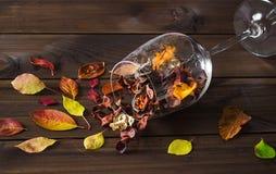 在一个酒杯的秋叶在木桌背景 免版税库存图片
