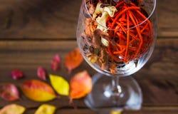 在一个酒杯的秋叶在木桌背景 库存照片
