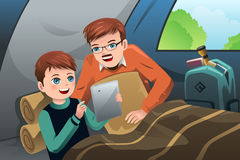 读在一个野营的帐篷的父亲和儿子一台片剂个人计算机 库存图片