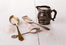 在一个量杯的喜马拉雅桃红色盐在木背景 免版税库存照片