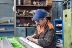 在一个金属切削机器的床的准备工作汇编的 锁匠进行一手工刮 免版税库存照片