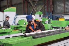 在一个金属切削机器的床的准备工作汇编的 锁匠进行一手工刮 免版税库存图片