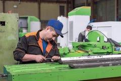 在一个金属切削机器的床的准备工作汇编的 锁匠进行一手工刮 库存照片