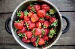 在一个金属平底锅的水多的草莓在木背景 免版税图库摄影