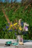 在一个金属杯子的野花有浮游物的 免版税库存图片