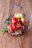 在一个金属篮子的红色有机苹果在木背景 图库摄影