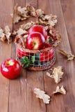 在一个金属篮子的红色有机苹果在木背景 免版税库存照片