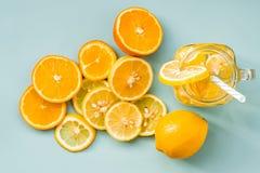 在一个金属螺盖玻璃瓶的柠檬水有用切片装饰的一根吸管的在蓝色背景的柑橘桔子和柠檬顶视图 免版税库存照片