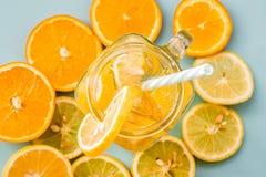 在一个金属螺盖玻璃瓶的柠檬水有用切片装饰的一根吸管的在蓝色背景的柑橘桔子和柠檬顶视图 库存照片