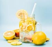 在一个金属螺盖玻璃瓶的柠檬水有用切片装饰的一根吸管的柑橘桔子和柠檬在蓝色背景 库存照片