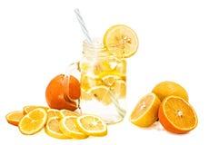 在一个金属螺盖玻璃瓶的柠檬水有用在白色背景和桔子隔绝的切片装饰的一根吸管的柠檬 免版税图库摄影