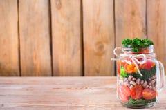 在一个金属螺盖玻璃瓶的健康素食主义者沙拉用豆 库存图片